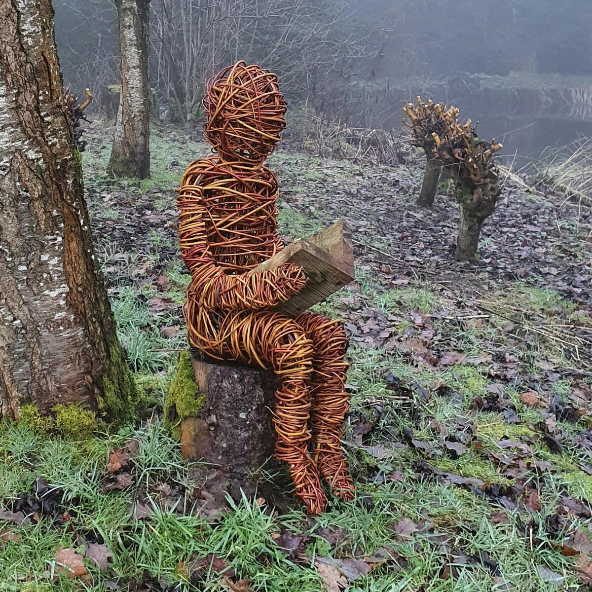 Willow man reading a book by the pond