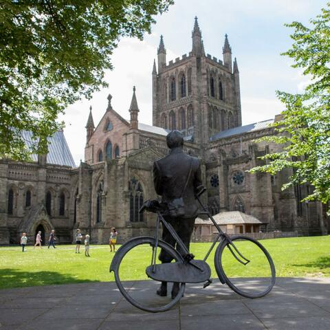 Statue of Elgar with his bicycle looking up at the Cathedral