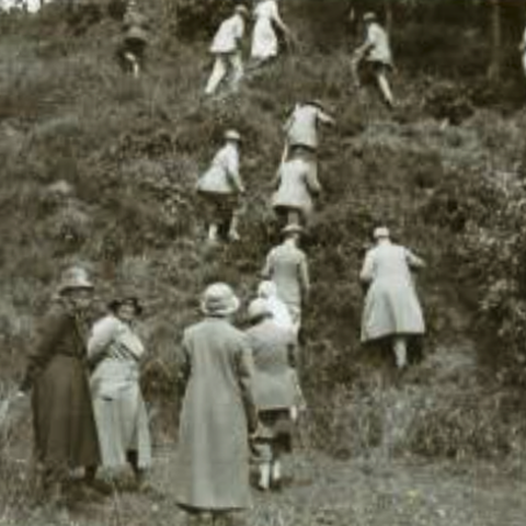Old photograph showing members of the old straight club climbing a steep mound